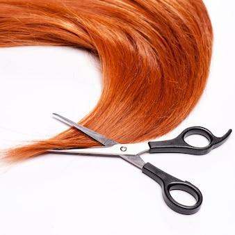 Glanzende rode haar en haar scherpe die scharen op wit worden geïsoleerd