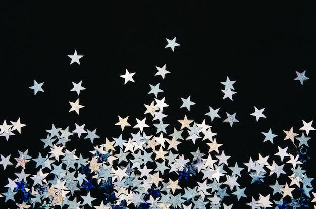 Glanzende sterren van folie op zwarte achtergrond.