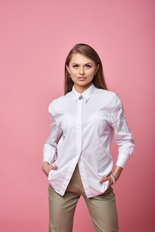 Glanzende zelfverzekerde vrouw die een wit overhemd draagt dat op roze achtergrond wordt geïsoleerd