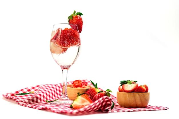 Glas aardbei cocktail soda geplaatst op een plaid tafelkleed geïsoleerd op wit