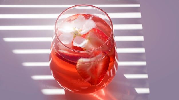 Glas aardbeiensangria met mousserende wijn op witte achtergrond met natuurlijk licht