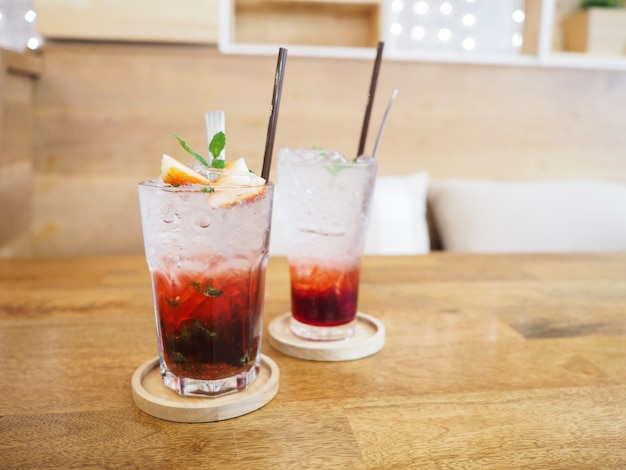 Glas aardbeiensap met frisdrank op houten tafel