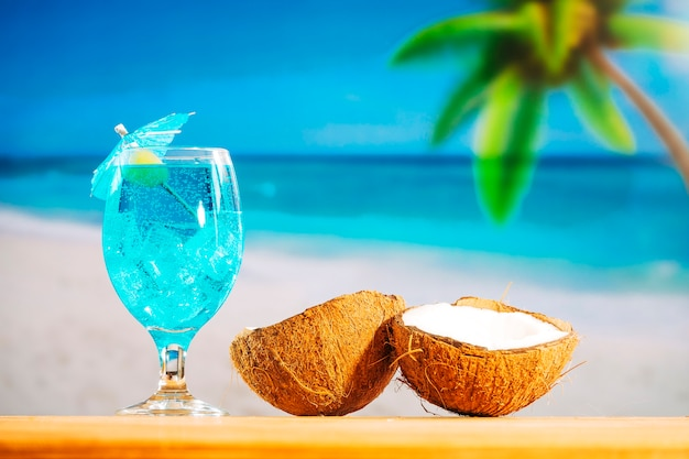 Glas afkoelende blauwe drank en gebarsten kokosnoten