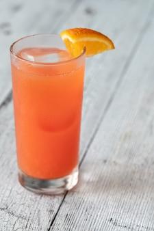 Glas alabama slammer-cocktail gegarneerd met sinaasappelwig