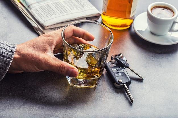 Glas alcohol hand man de sleutels van de auto en onverantwoordelijke bestuurder.