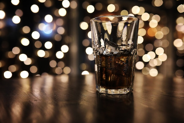 Glas alcohol met ijs op blured achtergrond met cirkel bokeh