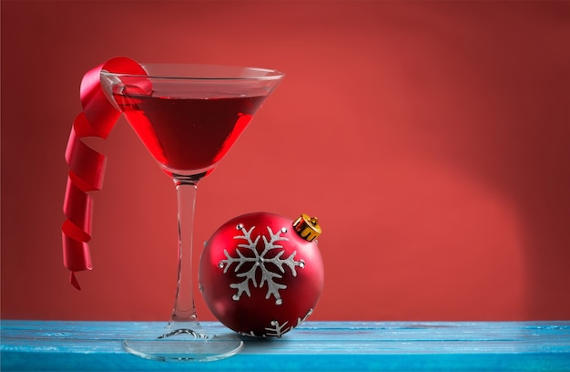 Glas alcoholcocktail en kerstmisbal op achtergrond