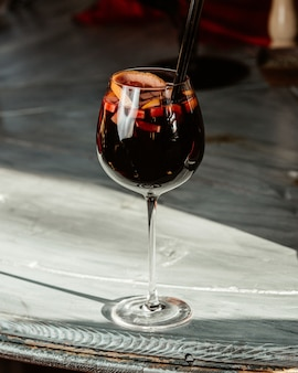 Glas alcoholische cocktail met stukjes sinaasappel en schil