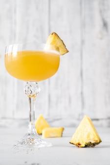 Glas algonquin-cocktail gegarneerd met ananasplak