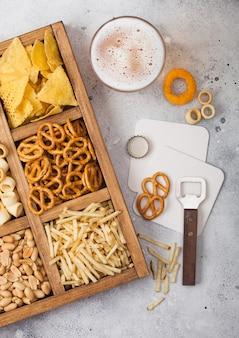 Glas ambachtelijk pils en opener met doos snacks op lichte keukentafel. pretzel, zoute aardappelsticks, pinda's, uienringen met nacho's in vintage doos met openers en bierviltjes.
