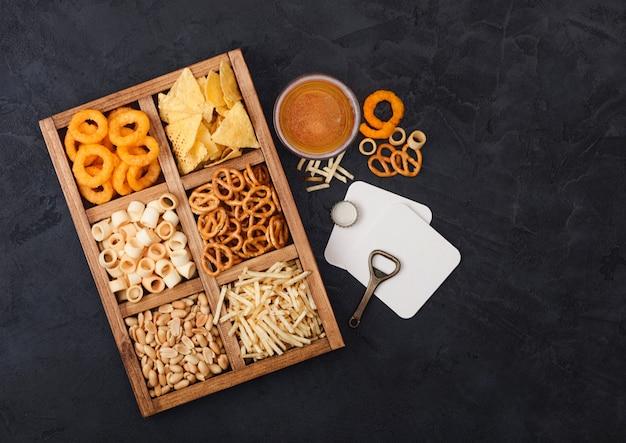 Glas ambachtelijke pils en opener met doos snacks op donkere achtergrond. pretzel, zoute aardappelsticks, pinda's, uienringen met nacho's in vintage doosje met openers en bierviltjes. bovenaanzicht