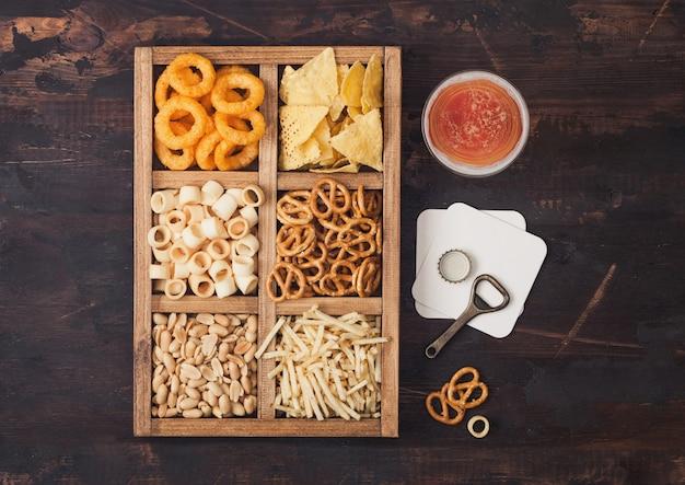 Glas ambachtelijke pils en opener met doos snacks op hout achtergrond. pretzel, zoute aardappelsticks, pinda's, uienringen met nacho's in vintage doosje met openers en bierviltjes.