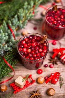 Glas amerikaanse veenbessendrank, amerikaanse veenbessen, pijpjes kaneel, anijsplantsterren op een houten achtergrond. kerst winter drankjes.