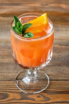 Glas belmont breeze cocktail gegarneerd met schijfje sinaasappel en verse munt