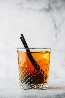 Glas bevroren zwarte thee met citroen die op heldere marmeren achtergrond wordt geïsoleerd. bovenaanzicht, kopieer ruimte. reclame voor café-menu. coffeeshop menu. verticale foto.