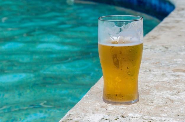 Glas bier aan de oever van het zwembad. glas met ijskoud biertje. bier drinken aan de rand van het zwembad