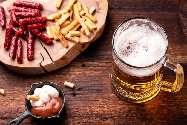Glas bier en snacks op een houten ondergrond.