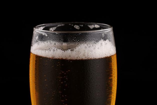 Glas bier licht op een donkere ondergrond