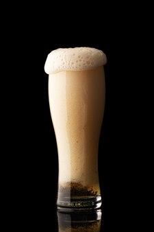 Glas bier met bubbels en dik wit schuim, geïsoleerd op zwarte achtergrond
