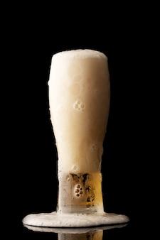 Glas bier met bubbels en dik wit schuim, geïsoleerd op zwarte muur