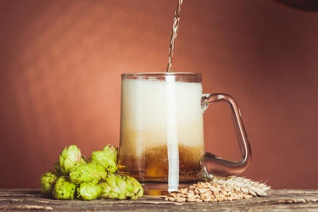 Glas bier met hop en gerst op de houten tafel