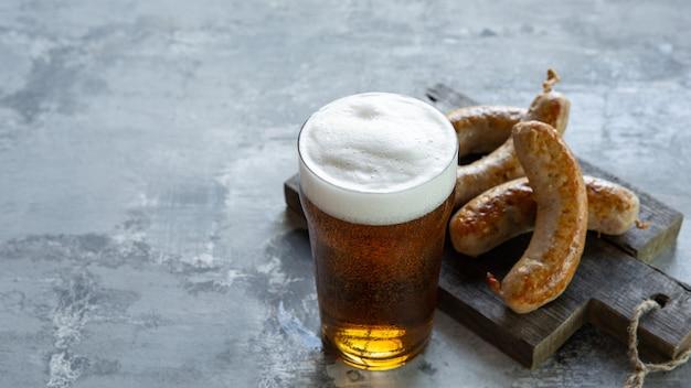 Glas bier met schuim bovenop op witte steenmuur.