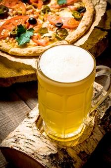Glas bier op de tribune van een berk en de pizza op de houten lijst