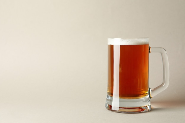 Glas bier op grijze achtergrond, ruimte voor tekst