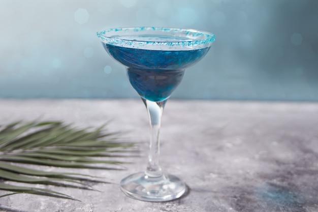 Glas blauwe cocktail met een palmblad