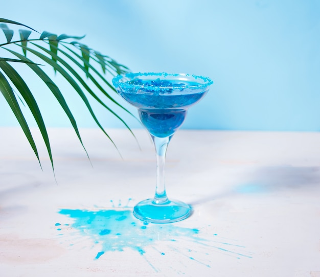 Glas blauwe cocktail onder een palmblad. hawaiiaanse cocktai, lagunecocktail, curacao.