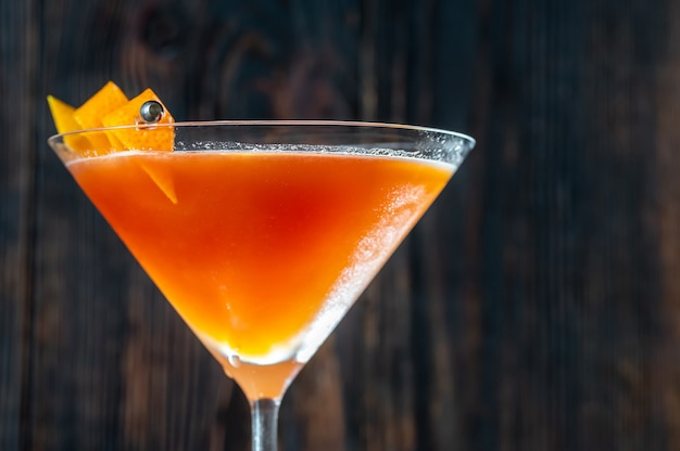 Glas bloed en zand cocktail in martini glas gegarneerd met sinaasappelschil