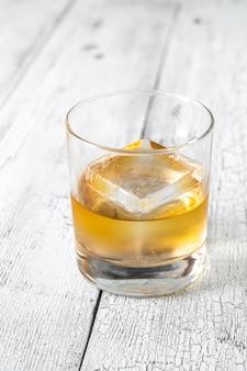 Glas bourbonwhisky met ijsblokje