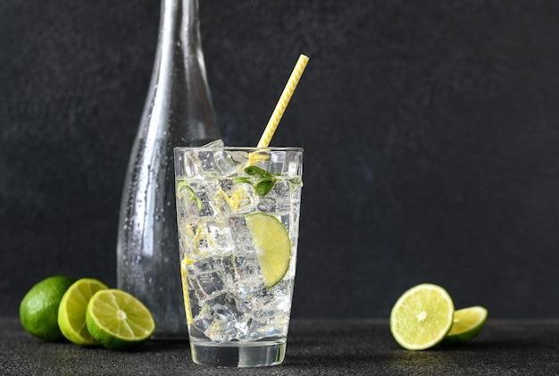 Glas bruisend water met ijsblokjes en schijfje limoen