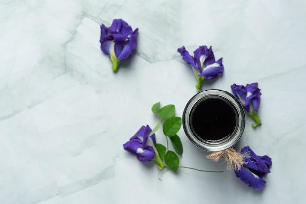 Glas butterfly pea flower thee op een witte marmeren vloer