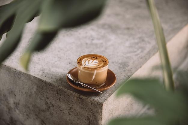 Glas cappuccino met latte art op schotel en met lepel op de concrete achtergrond met tropische plant ervoor
