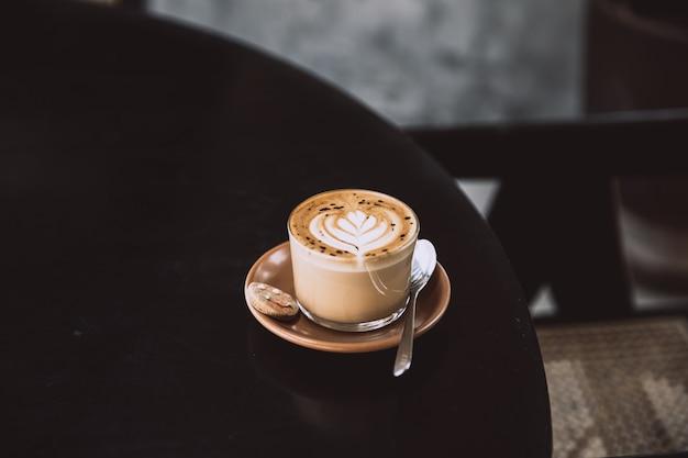 Glas cappuccino met latte art op schotel en met lepel op de zwarte tafel. ontbijt drankje