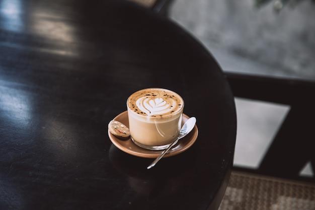 Glas cappuccino met latte art op schotel en met lepel op de zwarte tafel