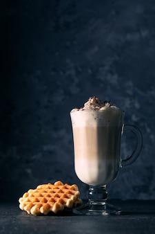 Glas cappuccino op een donkere achtergrond met plaats voor tekst. weense koffie met weense wafels.