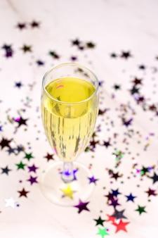Glas champagne en confetti in de vorm van sterren, bovenaanzicht, wazig