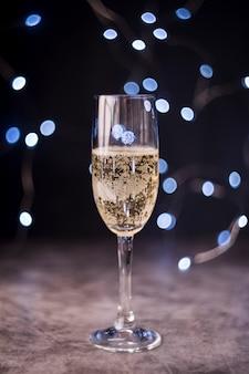 Glas champagne met bel over bokeh achtergrond