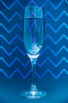 Glas champagne op het patroonachtergrond van zigzga