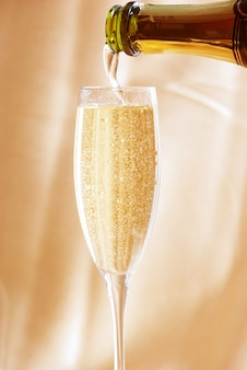 Glas champagne tegen gouden achtergrond