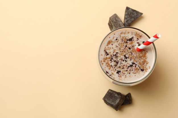 Glas chocolade milkshake en chocoladestukjes op beige achtergrond
