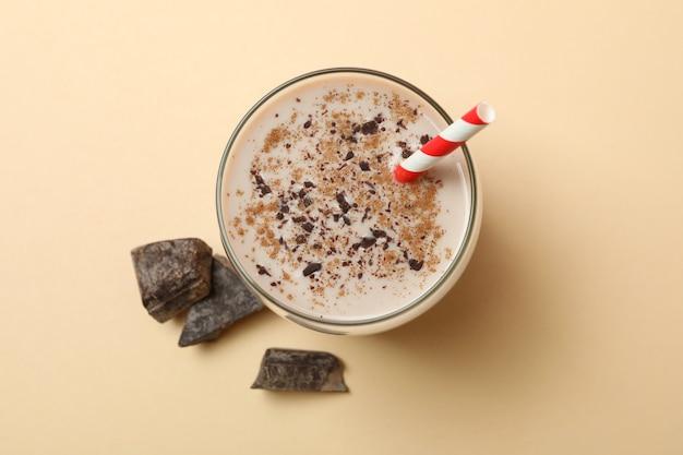 Glas chocolade milkshake en chocoladestukjes op beige muur