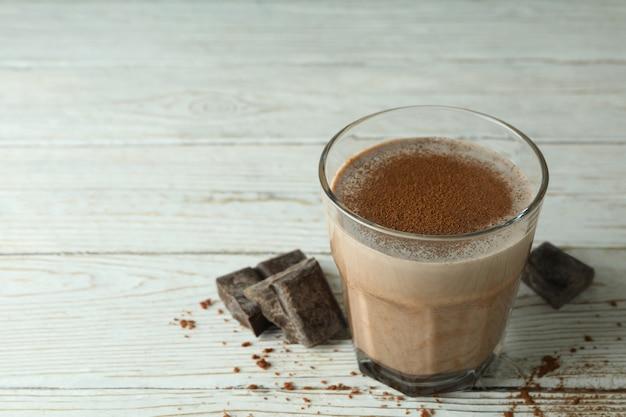 Glas chocolade milkshake en chocoladestukjes op houten tafel