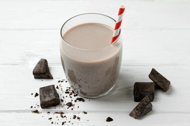 Glas chocolade milkshake en chocoladestukjes op witte houten tafel