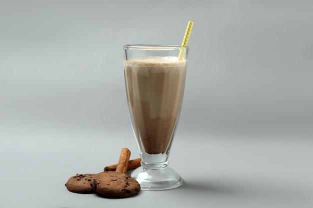 Glas chocolade milkshake, koekjes en kaneel op grijze achtergrond
