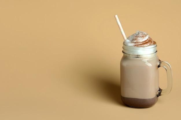 Glas chocolade milkshake met stro op beige achtergrond