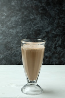 Glas chocolade milkshake op witte houten tafel