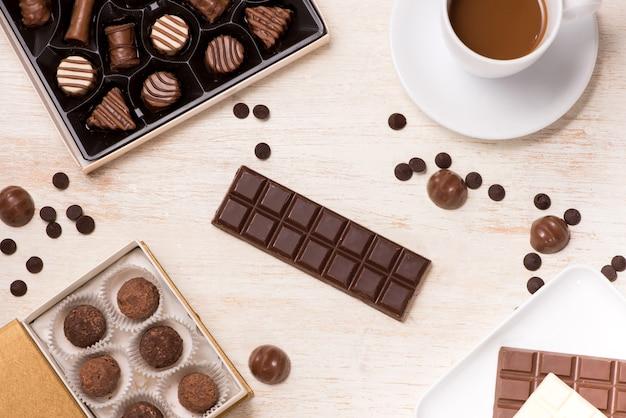 Glas chocolademelk en verschillende chocolaatjes op tafel